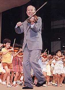 Dr. Shinichi Suzuki playing violin with children