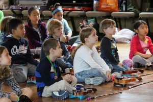 Several children about 5 or 6 years old, sit on the floor with violins on the floor in front of them. The children are listening to someone outside the frame speak.