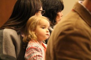 A blonde girl, about 2 years old, focuses her attention on something not visible while sitting on an adult woman's lap.