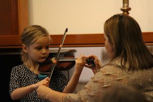 An adult woman assists a young girl, about five years old, with holding a violin correctly.