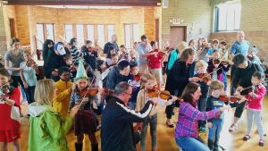 In a crowded classroom, dozens of parents kneel on the floor to assist their school-age children with holding their violins.
